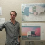 "A white man with short brown hair, wearing a grey dress shirt and black slacks, is standing to the left of a series of architectural renderings and sketches that have been pinned to a wall for critique. Some of the renderings are computer-generated and in bright colors of blue and pink. Some of the renderings are smaller black and white sketches of architectural details. The top drawing is labeled ""Porchdog House,"" and the project appears to be for a modernist, white beach house."