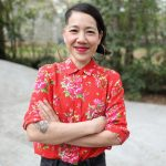 Portrait of Hong-An Truoung. She is a thin woman with short, straight black hair parted on the right side of her head. She has big hoop earrings on, a bright red shirt with pink flowers, and her arms crossed in front of her chest. She is smiling with her mouth closed. In the background, out of focus, there is a landscape with gray stone wall, green trees, and a view into a yellow-green field.
