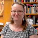 Photograph of JJ Bauer, a white woman with shoulder length straight dark blond hair, wearing glasses and a grey short-sleeved top and standing in front of a bookcase