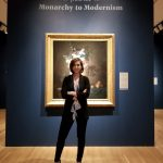 """Photo portrait of Kelsey Martin standing in front of a painting from the exhibition """"Women Artists in Europe from the Monarchy to Modernism,"""" She is wearing a grey blouse, black slacks, black blazer, and black pumps. Her hair is brunette and chin length. She is standing in front of a still life of flowers and fruit."""