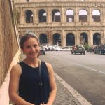 Rachel is wearing a black tank top, has her brunette hair in a bun, and is smiling because she is standing in front of the Coliseum in Rome.