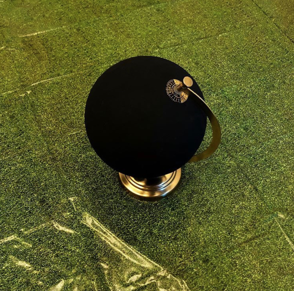 Photograph of a globe painted black and sitting on a greenish vinyl tile floor.