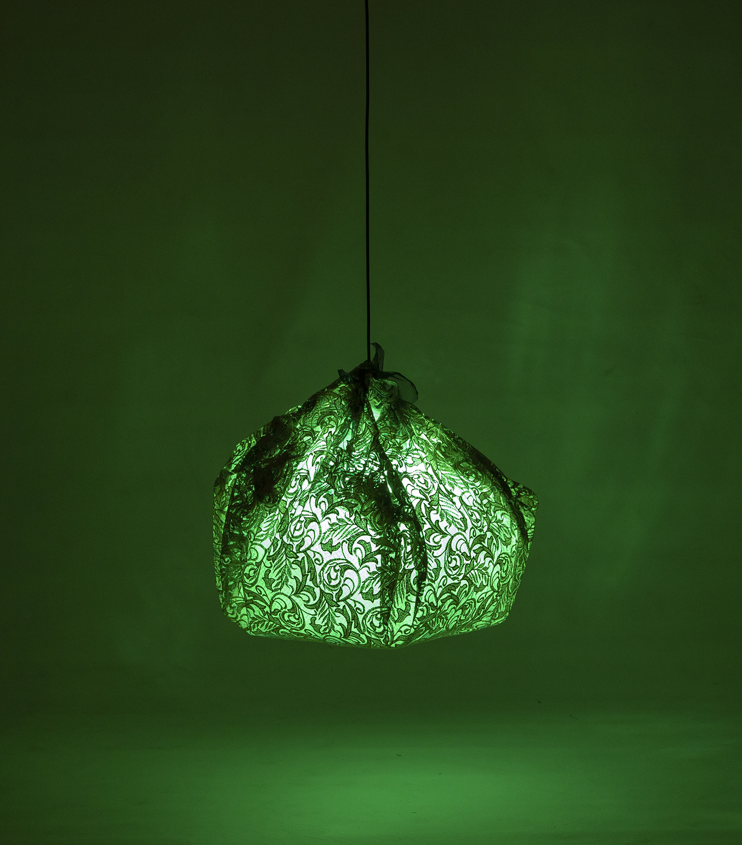 Image of a hanging lamp wrapped in green fabric and casting a green light